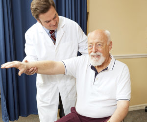 doctor doing flexibility exercise to elderly patient