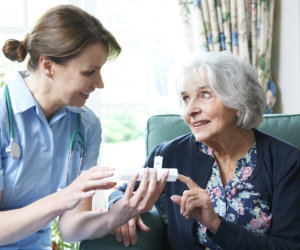 caregiver giving daily medicine to elderly patient