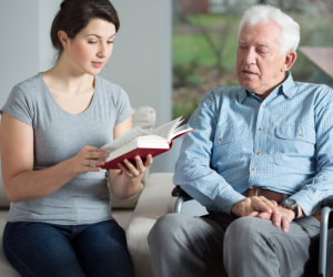 caregiver reading a book to elderly patient