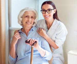 caregiver holding the hands of elderly patient